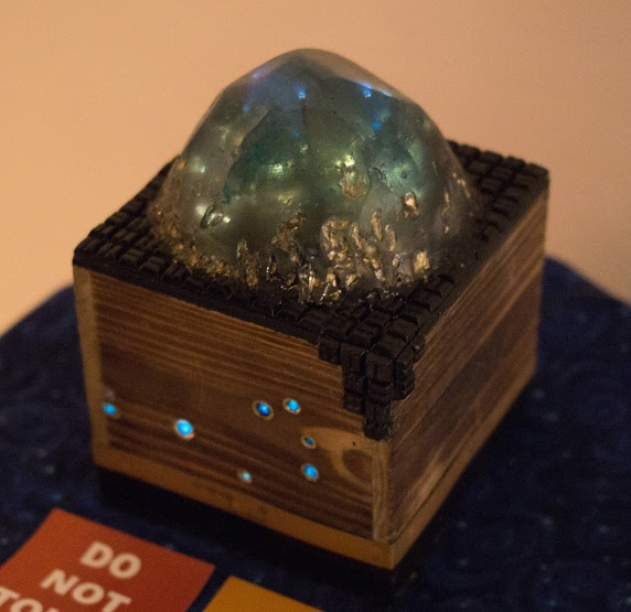 Third Place, Fine Art Category, a crystal-like sculpture glows atop a box