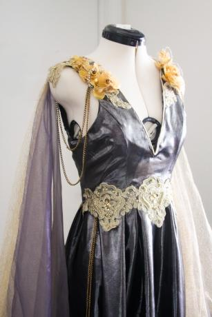 A long, sleeveless dress made from grey metallic fabric with layers of gold & purple, a gold lace belt, & gold flowers.