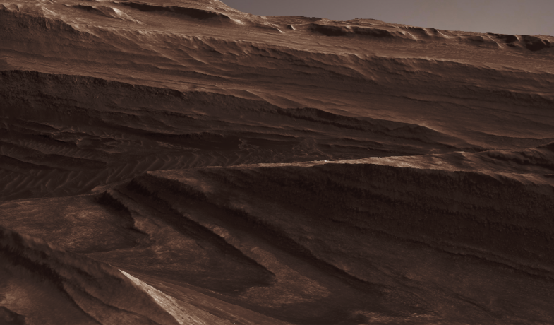 A view of two reddish-brown cliffs on either side of a canyon; on the edge of the foreground cliff is a tiny white figure.
