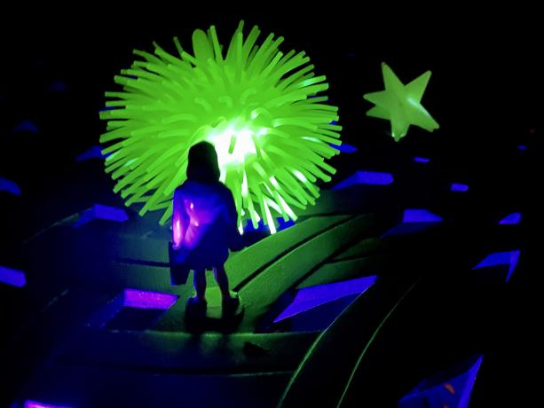 Humous childlike staged photo of a toy person confronting a glowing ball and star that are backlite with a UV flashlight.
