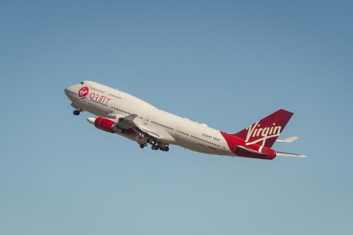 A Virgin Orbit airplane carrying a rocket under it's wing lifts off from the runway.