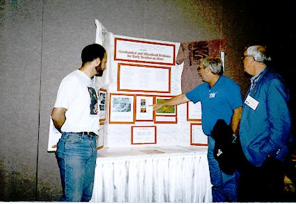 Clemmett, Gibson, and McKay looking at a poster