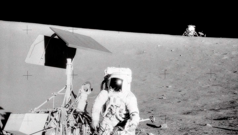 NASA astronaut Pete Conrad standing next to Surveyor 3 with the Apollo 12 Lunar Module Intrepid in the background. (NASA photo by Alan Bean)