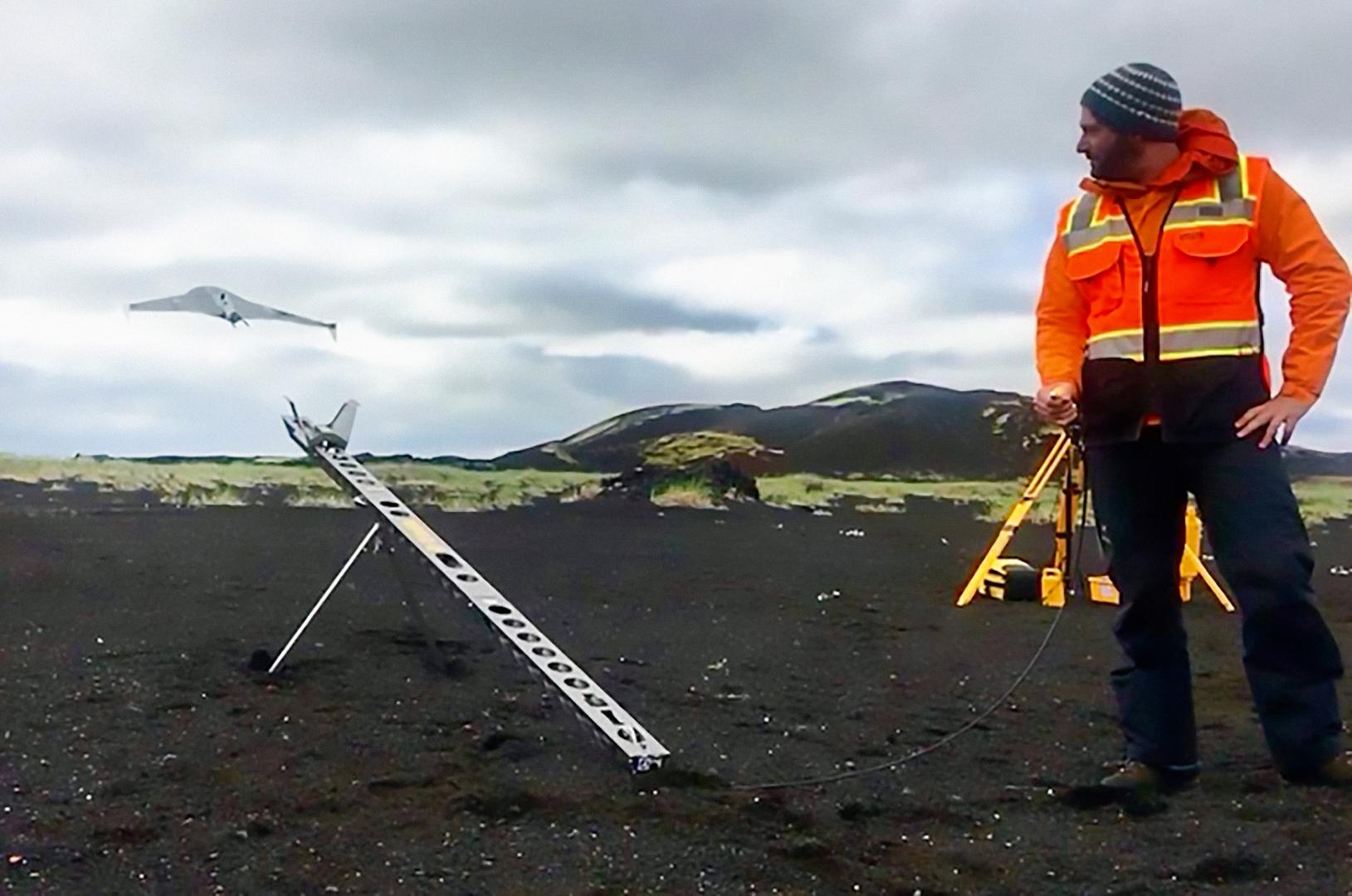 """Christopher Hamilton launches a drone during flight tests in the Holuhraun, Iceland lava flow field. RAVEN builds upon recent developments in drone technology – such as NASA's Ingenuity Mars Helicopter, accompanying the Mars 2020 rover """"Perseverance."""""""