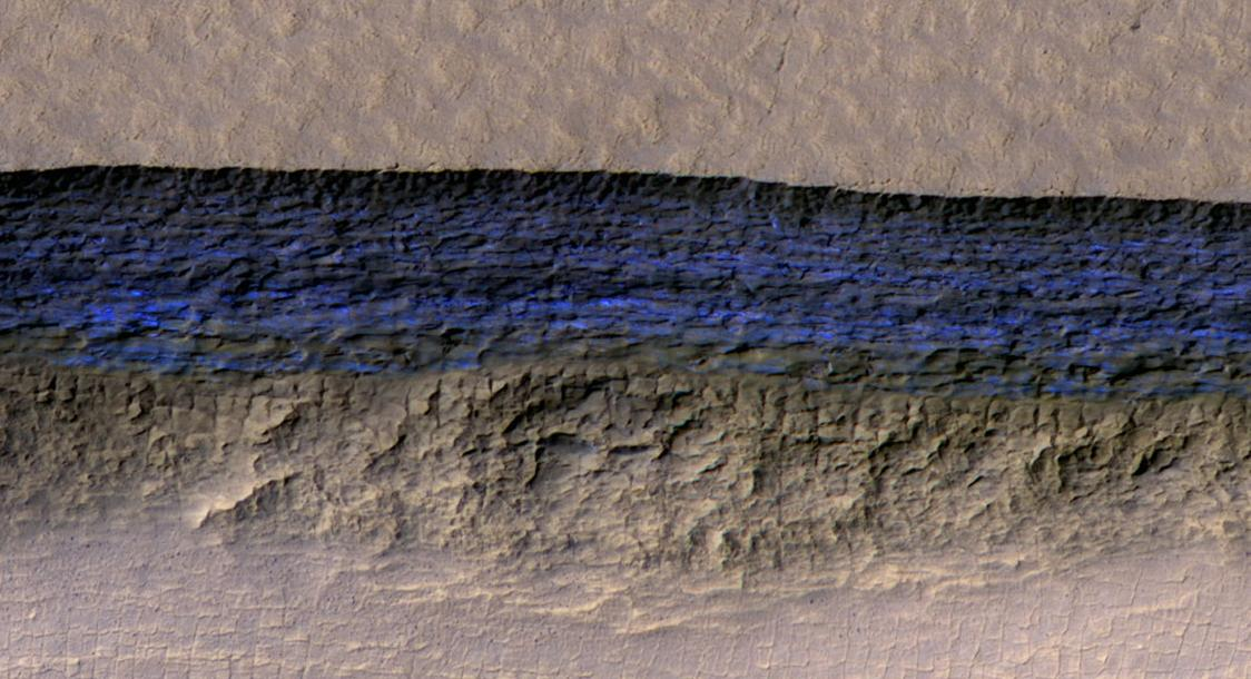 At this pit on Mars, the steep slope at the northern edge (toward the top of the image) exposes a cross section of a thick sheet of underground water ice. The image is from the HiRISE camera on NASA's Mars Reconnaissance Orbiter, with an enhanced-color central swath between grayscale on each side. (Image: NASA/JPL-Caltech/UA/USGS)