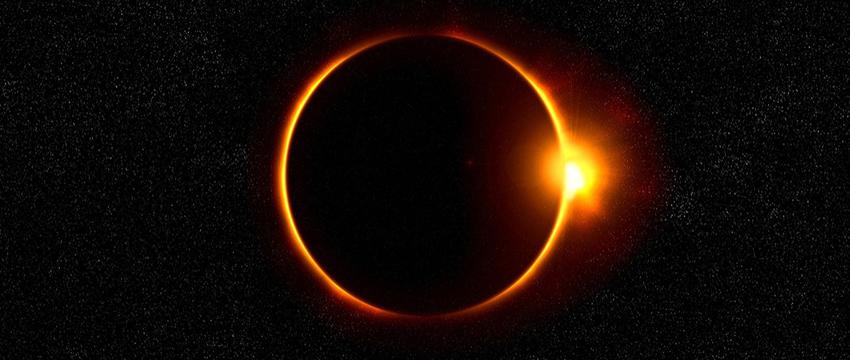 The sun is eclipsed by the moon against a starry background.