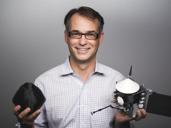 LPL Professor Dante Lauretta, OSIRIS-REx PI, with models of Bennu and spacecraft