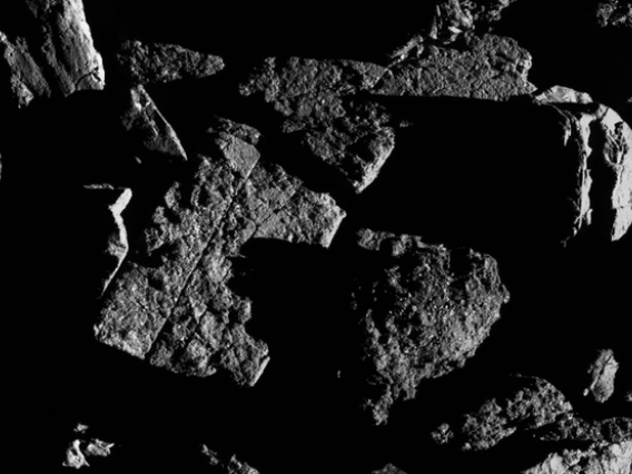 This image, taken by the spacecraft from a distance of 0.4 miles, shows a group of large boulders located just north of asteroid Bennu's equatorial region, with two exhibiting linear cracks. For scale, the crack that runs through the rectangular boulder (
