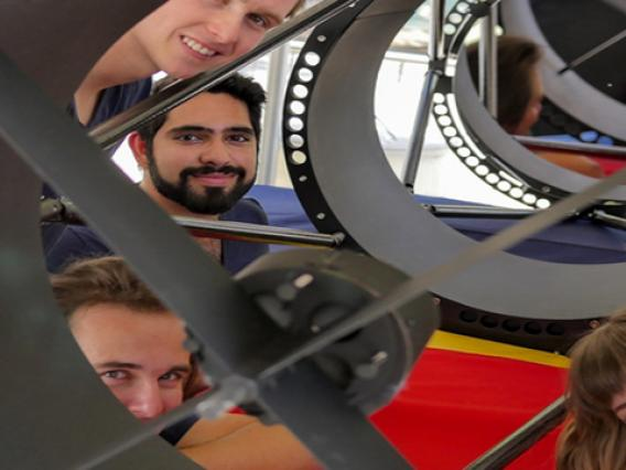 Undergraduate students Ryan Bronson, Sameep Arora, Damon Marco Colpo, Lindsie Jeffries, and Evelyn Hunten peer out from a telescope they built to track satellites.